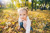 little smiling blond cute toddler girl at autumn city park fall season