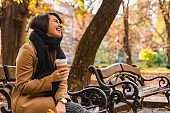 woman sitting on the bench at autumn city park drinking coffee