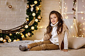 beautiful little child girl sitting in room