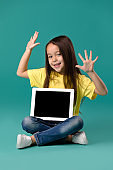 little girl holding a blank tablet computer