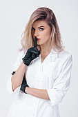 cosmetologist in black gloves shows sign silence. Woman beautician doctor