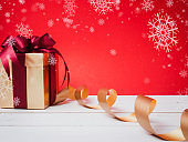 Valentine festival , New year Gold gift box with red ribbon. Red background and snowflake for create idea copy space.