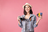 Tourist woman in summer casual clothes.Asian Smiling woman .Passenger traveling abroad to travel on pink background.She going to summer vacation.Travel trip funny Credit card on holiday.