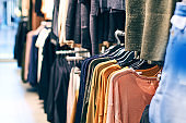 Interior of fashion clothes store with different women clothes on hangers in various colors.