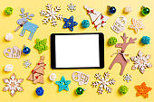Top view of digital tablet on yellow background with New Year toys and decorations. Christmas time concept