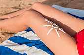 Woman sunbathing on the beach with a drawing of sun on her leg with sunscreen cream