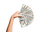 Female hand holding a fan of dollar banknotes on isolated background. Succes and investment concept