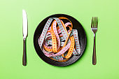 Top view of heap of colorful measuring tapes in plate on green background. Diet concept with copy space