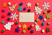 Top view of craft envelope on red background made of holiday decorations and toys. Christmas ornament concept