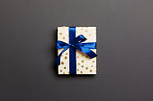 wrapped Christmas or other holiday handmade present in paper with blue ribbon on black background. Present box, decoration of gift on colored table, top view with copy space