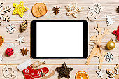 Top view of tablet on holiday wooden background. New Year decorations and toys. Christmas concept