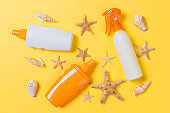Sunscreen bottles with seashells on yellow table top view
