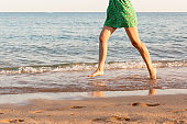 Leg of woman running on beach with water splashing. summer vacation. legs of a girl walking in water on sunset
