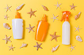 sunscreen cream with starfish and seashells in bottles on yellow background, top view