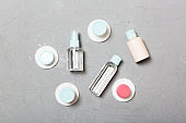 Group of small bottles for travelling on gray background. Copy space for your ideas. Flat lay composition of cosmetic products. Top view of cream containers with cotton pads