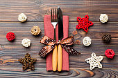 Top view of holiday set of fork and knife on wooden background. Close up of Christmas decorations and toys. New Year Eve concept