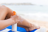 Girl is using spray to apply sun cream on her leg at the beach