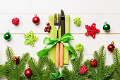 Top view of christmas decorations on wooden background. Fork and knife on napkin tied up with ribbon and empty space for your design. New year pattern concept