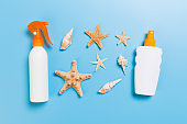 Sunscreen bottles with seashells on blue table top view
