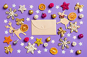 Top view of craft envelope surrounded with New Year toys and decorations on purple background. Christmas time concept