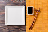 Empty white square plate with chopsticks for sushi and soy sauce on wooden background. Top view with copy space