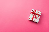 Valentine or other holiday handmade present in paper with red hearts and gifts box in holiday wrapper. Present box of gift on coral colored table top view with copy space, empty space for design
