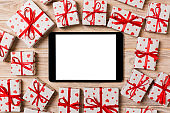Online shopping holiday background. Tablet screen with copy space on wood with gift box and heart top view. Advertising mockup. Valentine day internet sales concept