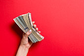 Top view of female hand holding a thick pack of different dollar bills on colorful background. Wage and salary concept with empty space for your design