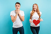 shocked man, learns about the pregnancy of his wife, a pregnant woman holding a red paper heart against the belly
