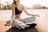 Young woman in sportswear sitting outdoors relaxing meditation taking sun rays