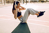 Image of beautiful young athletic fitness woman doing sports exercise, morning outdoors listening to music with headphones.