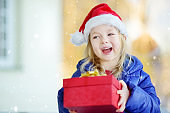 Adorable little girl wearing Santa hat holding Christmas gift on beautiful winter day