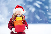 Adorable little girl wearing Santa hat holding a pile of Christmas gifts on beautiful winter day