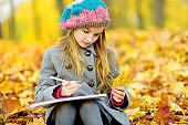 Cute little girl sketching outside on beautiful autumn day. Happy child playing in autumn park. Kid drawing with colourful pencils.