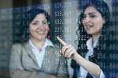 Busineswomen analyzing stock market data on Graphical User Interface