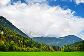 Breathtaking landscape of mountains, forests and small Bavarian villages in the distance. Scenic view of Bavarian Alps with majestic mountains in the background.
