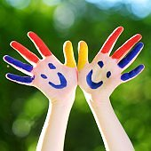 Adorable little kid with hands painted having fun outdoors
