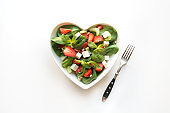 Fresh salad of strawberry, celery, spinach, pine nuts, cheese in plate as heart on white. Concept clean eating for Detox.