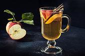 Glass of warm apple tea with lemon and cinnamon on black table. Fall still life.