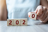 Business woman hand holding wooden cube with 2020 word on table background. Resolution, strategy, solution, goal, business, New Year New You and happy holiday concepts