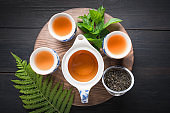 Tea ceremony. Three cup of tea with mint and kettle on dark . Chinese tea concept. View from above.