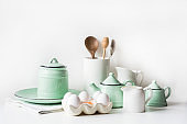 Crockery, tableware, utensils and other different white and turquoise stuff. Kitchen still life.