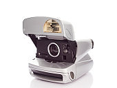 Metalic silver colored Instant film camera from 90's on white background