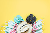 Outfit for beach and tropical vacations, straw beach sunhat,towel, sun glasses on yellow. Summer concept.