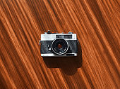Rangefinder film camera on a wooden table from directly above