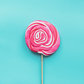Lollipops candy swirl white and pink on pastel blue.