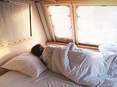 girl sleeping on bed at camper van