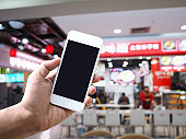Hand holding mobile phone over Chinese noodle restaurant blur background.
