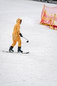 Man dressed as giraffe on a snowboard