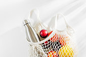 Cotton net bag with reusable metal water bottle and fruits. Sustainable lifestyle.  Eco friendly concept.